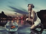 Woman looking at goldfish in a bowl