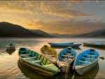 colored rowboats on a lake at sundown