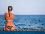 girl in a bikini sitting on a pier
