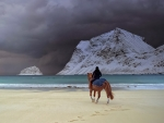 riding a horse on a beach in winter
