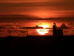 silhouette of lighthouse at sunset