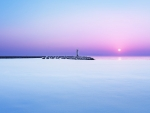 lighthouse on pier at dawn