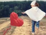 Little girl and heart kite