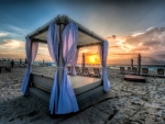 canopy bed on a beach at sunset hdr