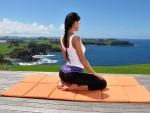 girl doing yoga over hawaiian seashore