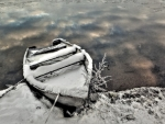 snow covered boat on a lake shore