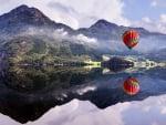 hot air balloon reflected in mountain lake