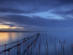 broken pier posts at sunset
