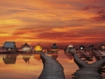 houses on stilts at gorgeous orange sunset