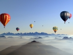 hot air balloons above the foggy hills