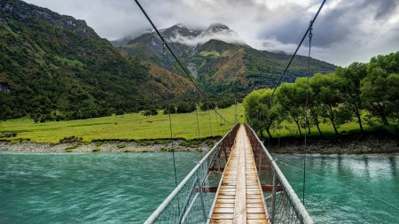 bridge over turquoise rver - grass, bridge, turquoise, clouds, mountains, river