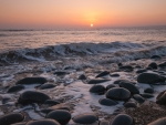sea waves over smooth beach stones at sunset