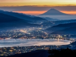 mt fuji in the background of a city at dusk
