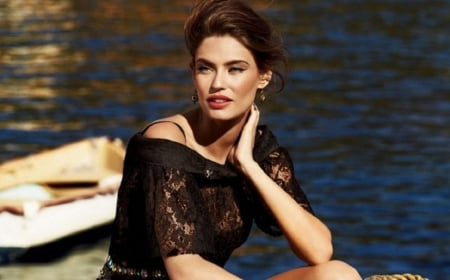 Bianca Balti - elbow on knee, water, black lace top, earrings, looking away, sitting on boat dock, red hair, left hand on face
