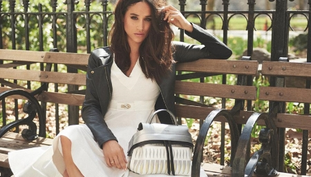 Meghan Markle - iron railings, dark grey leather jacket, brunette, ornamental clasp, sitting on park bench, with handbag, white dress, ring on finger