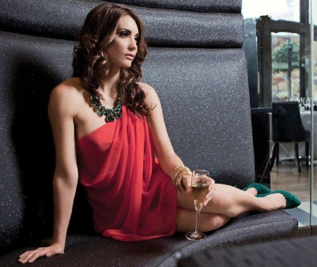 Tanit Phoenix - red sheer dress, bracelets, green high heels, posing on corner seat, brunette, see thru, large necklace, tall glass