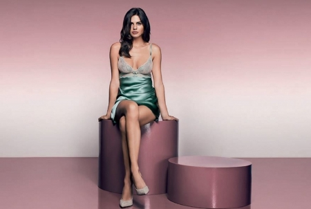 Bojana Krsmanovic - brunette, wall is a purple gradation, light purple backgroud, sitting on circular pieces, heels, long hair, green slip