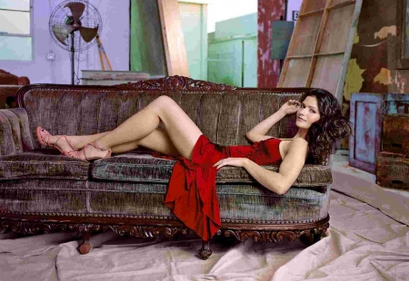 Jill Hennessy - brunette, wood pieces, paint cloth on floor, paint wash on cupboard, red dress, posing on couch, pedestal fan, pink heels with straps