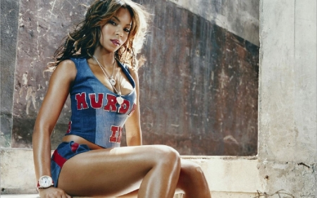 Brunette singer Ashanti - brunette, blue and red top and shorts, sitting, two piece outfit, wall