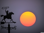 Big sunset behind wind vane