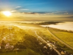 Aerial View of Sunbeams over Foggy Landscape