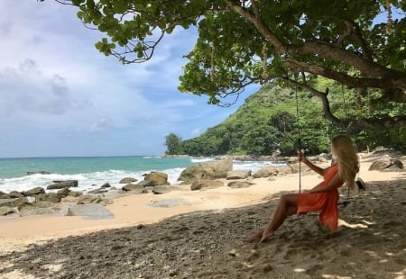 Anjelica Ebbi relaxing by the seashore - ash blonde, shade, large tree with swing, trees, tree swing, salmon pink dress, sandy beach, sea, bracelet on right arm