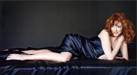 Christina Hendricks - red hair, satin, electriv royal blue dress, grey eyes, posing on couch
