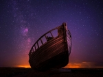 Small, old boat contrasted against starry sky