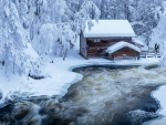 Snowy Log Cabin at Kitkajoki river in Finland