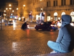 Person sitting in golden lights of street