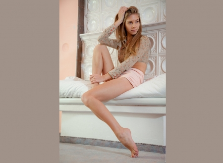 Anjelica Ebbi - pink shorts, grey blouse, bare feet, decorative walls, blonde, sitting on bed, long legs