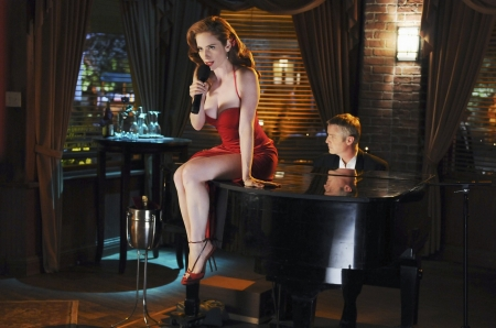 Jaime Ray Newman - microphone, red hair, singing, on top of piano, red dress and heels