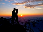 Couple kissing on mountaintop at sunset