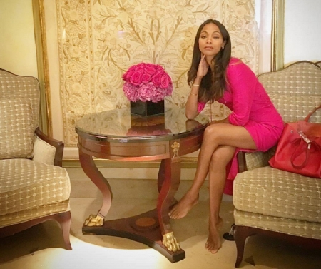 Zoe Yadira Saldana Nazario - brunette, bare feet, thigh exposed, sitting on arm of couch, hot pink dress, bag, flowers, round coffee table