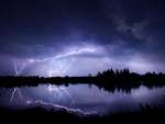 Lightning storm over lake during purple midnight