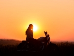 Lady on motorcycle looking off into a somber sunset