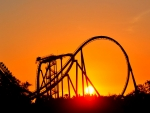 Roller coaster backdropped by sunset during golden hour