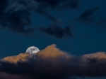 Bright moon peaking over russet clouds during a soft blue night