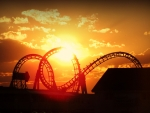 Sunset pierces through amusement park roller coaster during golden hour