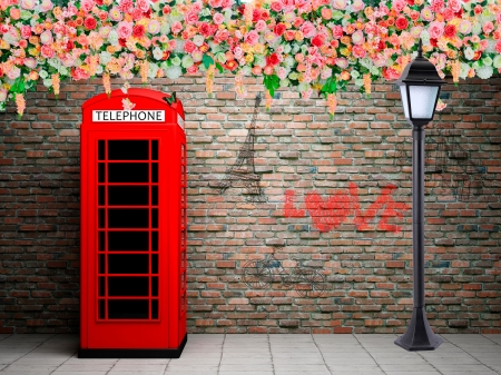 Red telephone booth at the brick wall - red, telephone, brick, flowers, booth, wall, light, roes, beautiful