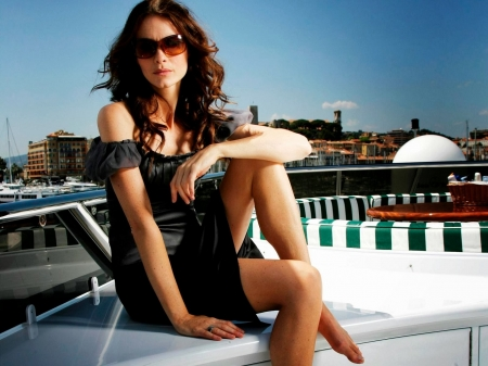 Saffron Burrows - nice legs, black dress, brunette, sunglasses, posing on a speedboat, ring on finger