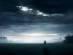 Hooded man running through field under grey sky