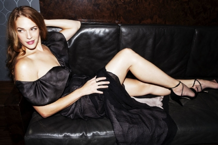 Amanda Righetti - black leather, Red Hair, long dress, high heels, black with off shouldeer puffe sleeves, posing on couch