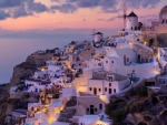 Greek houses on a hill by the water during a pink sunset