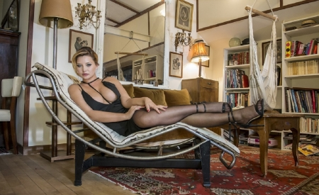 Anna Polina - sofa, heels, carpet, posing in recliner, swing chair, wood floors, lamps, black dress and stockings, coffee table, brunette, books and shelves