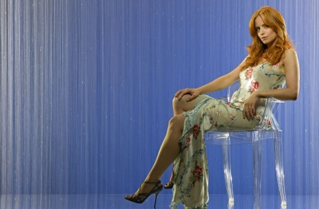 Jaime Ray Newman - beige dress, red head, with paterns, grey heels, see thtru plastic chair, ring on finger