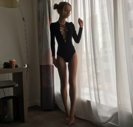 Ekaterina Zueva as a blonde - long legs, sheers, criss cross opening in front, shelf, blonde, hair is tied into a bun, black body suit