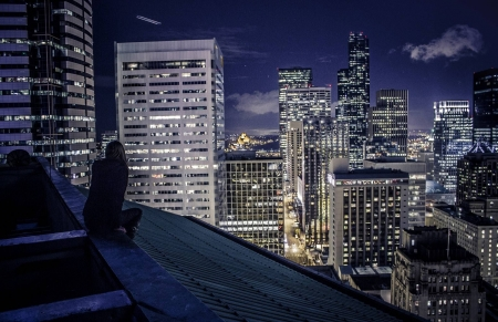 Woman sits on top of building in a big city - somber, cityscape, dark, sky, woman, night, skyscraper, rooftopping, clouds, skyscrapers, city