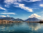 City of Antalya by the water, backdropped by mountains and a blue sky