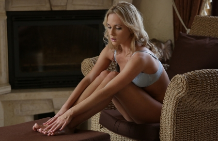 Vinna Reed - brunette, lamp, blue bikini lingerie, hands on feet, cushions, rattan arm chair, leaning forward, fire place
